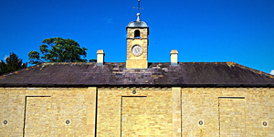 an image of an old roof with a clocktower peering over the top of the roof