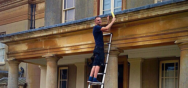 an image of a man standing on a ladder, leaning against a stately home to fix the roofing