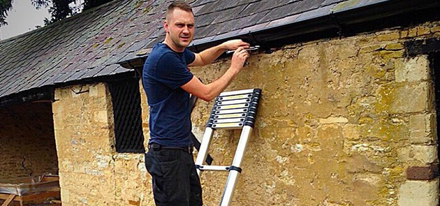 a close-up image of a man on ladder using pliers to fix the guttering system