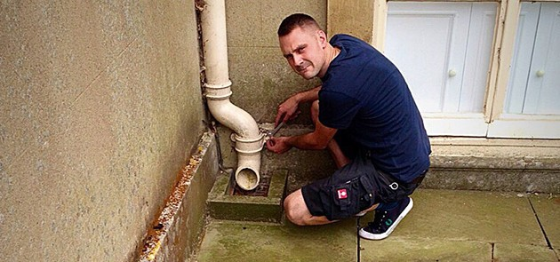 a close-up image of a man fixing a guttering system attached to a customer property
