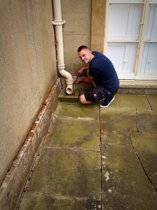 an image of a man crouching on the ground to fix a broken guttering system