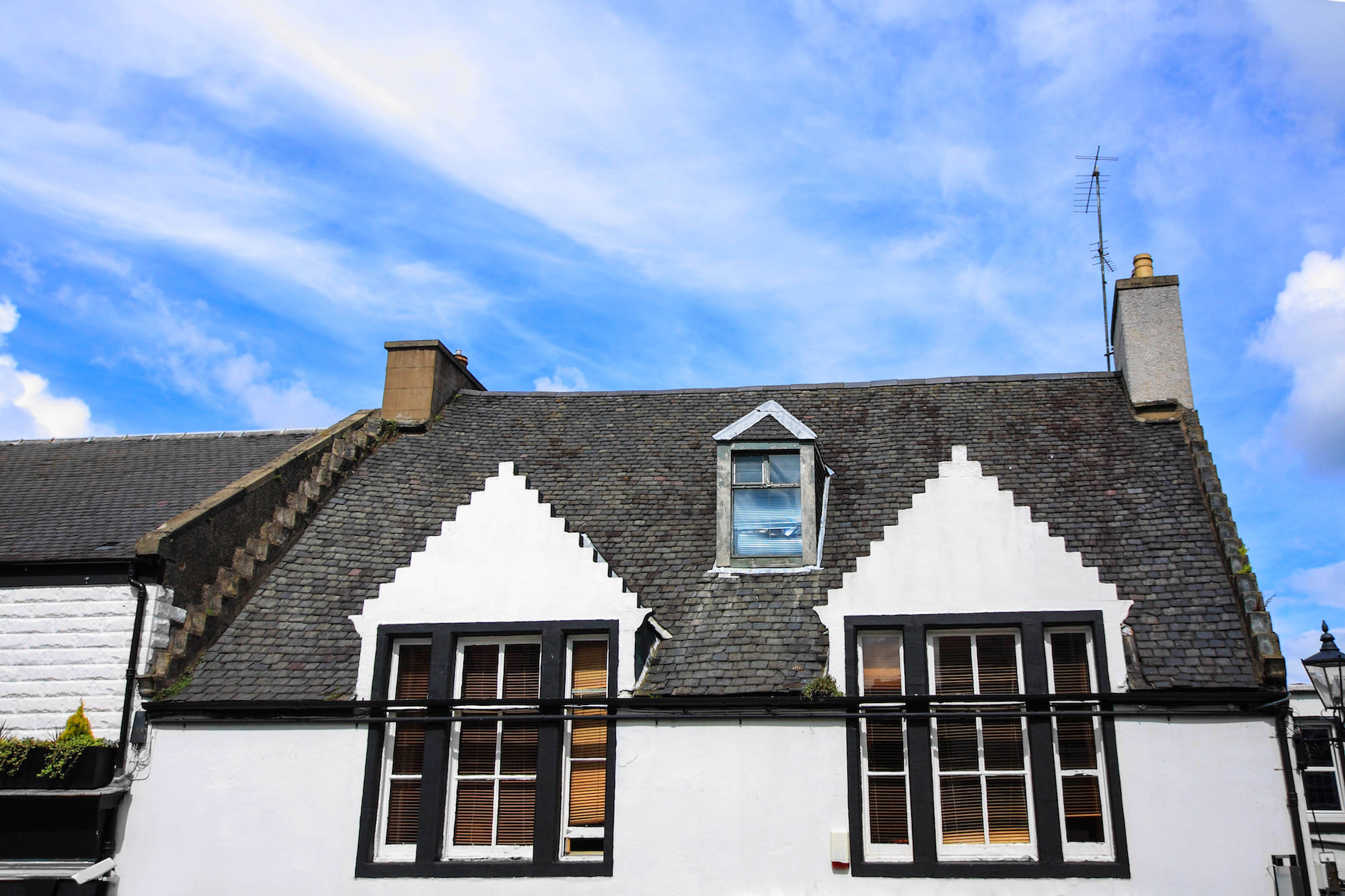 a picture of a house with a big cast iron guttering system installed