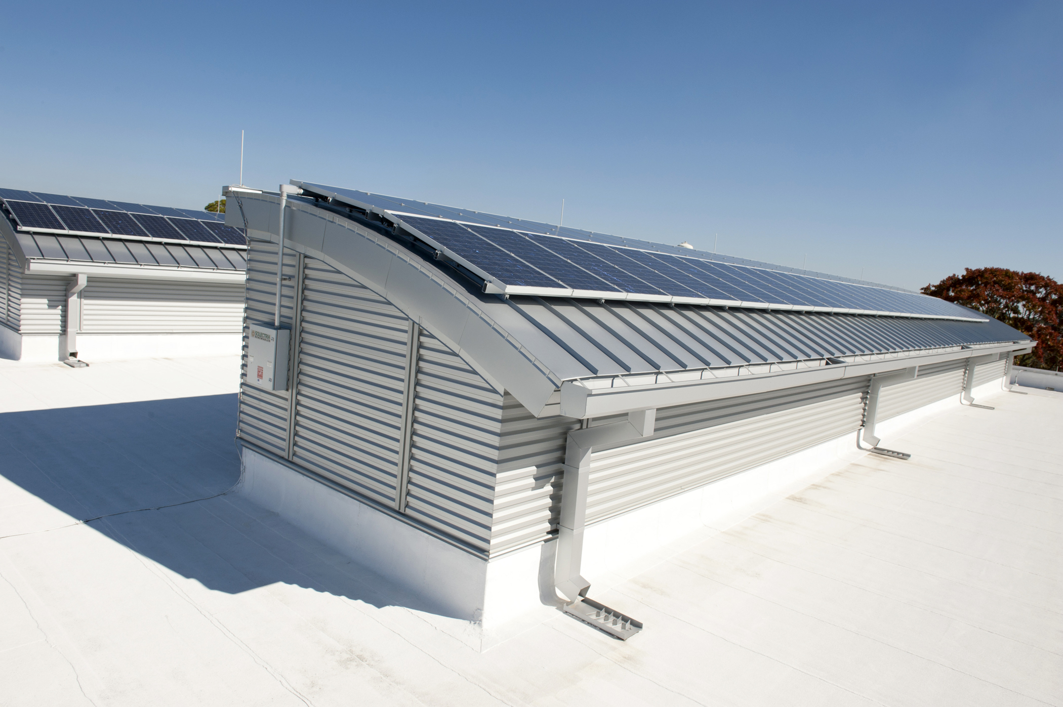 an image of a commercial roof that has been designed sustainably using solar panels and 'cool roof design' techniques