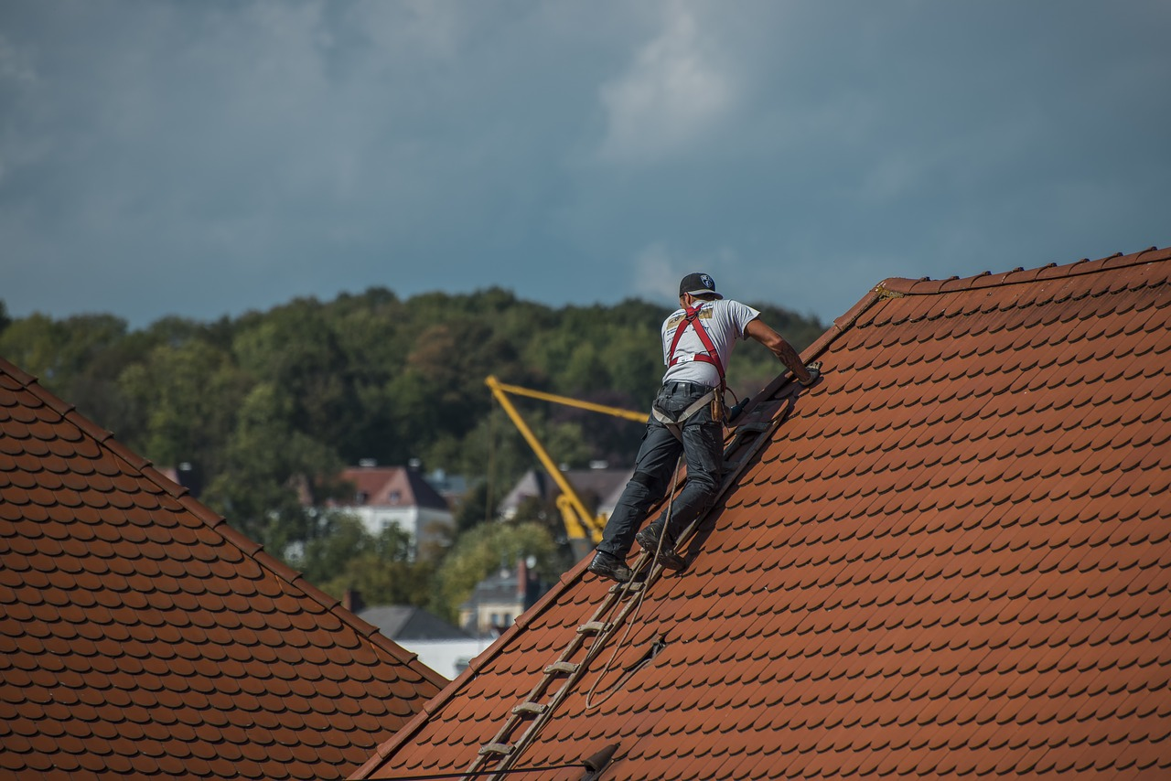Image of someone working on a roof, repairing tiles