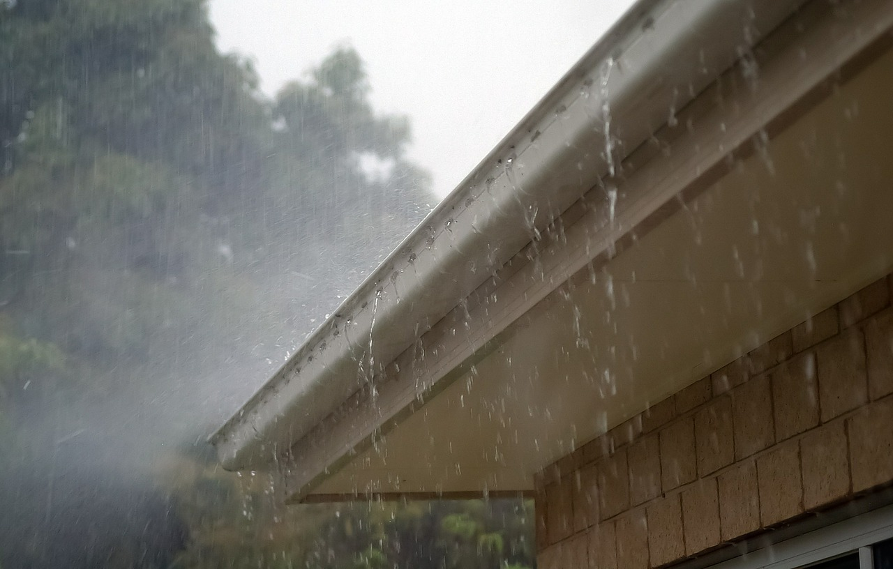 A close up photo of rain cascading of a home gutter