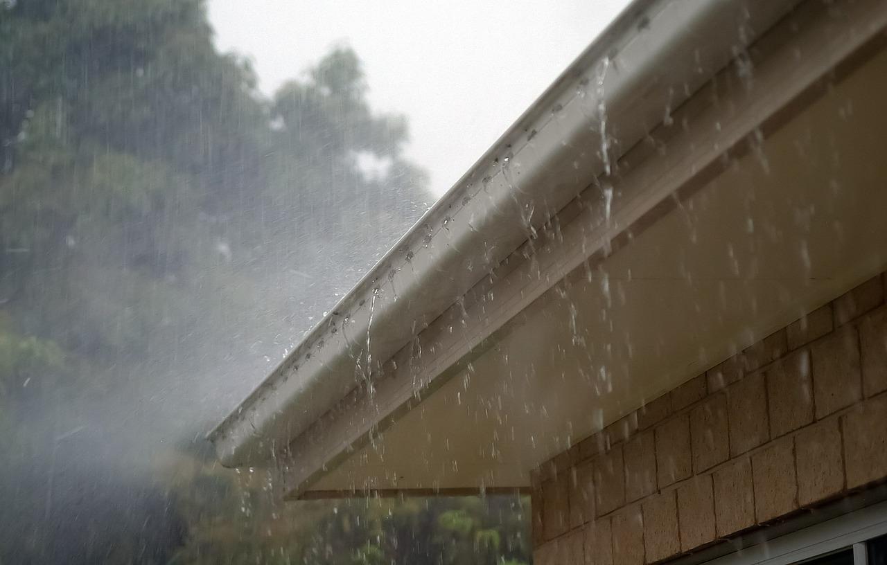 A close up photo of rain cascading of a home gutter