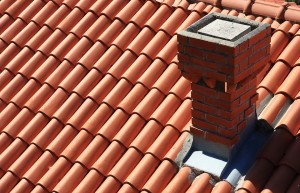 An image of a clay roof with a small chimney