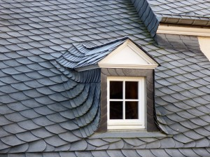 An image of a slate roof with a small window