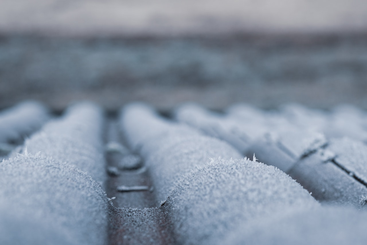 An image of roof tiling covered in frost, a common cause of roof damage in winter. Roof restoration may be required if damage causes a leak in winter.