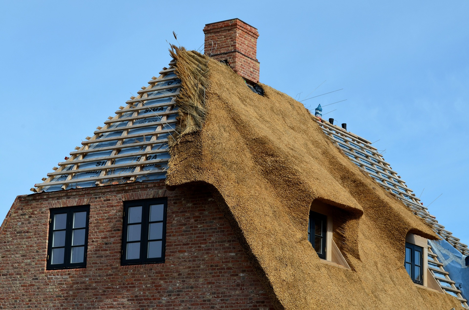 A thatched roof partway through construction.